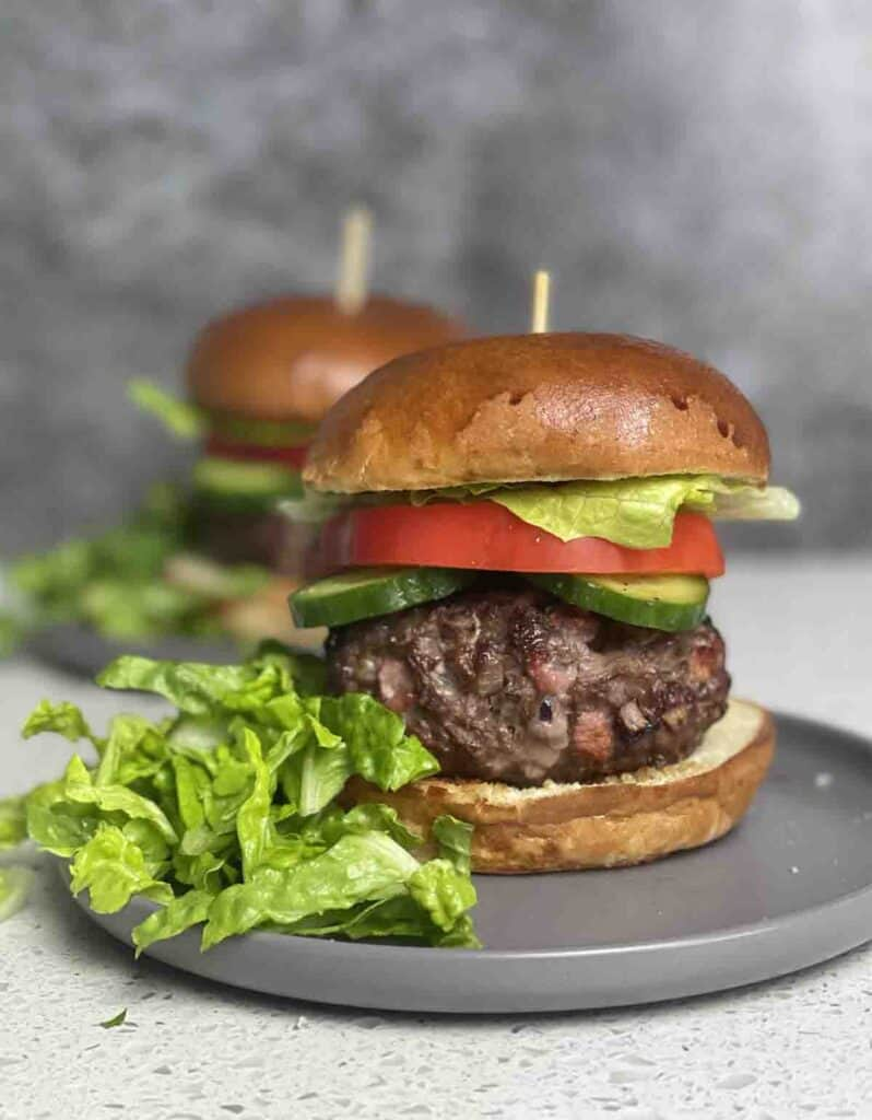 venison burger in a bun with cucumber and peppers on a plate with salad on the side.