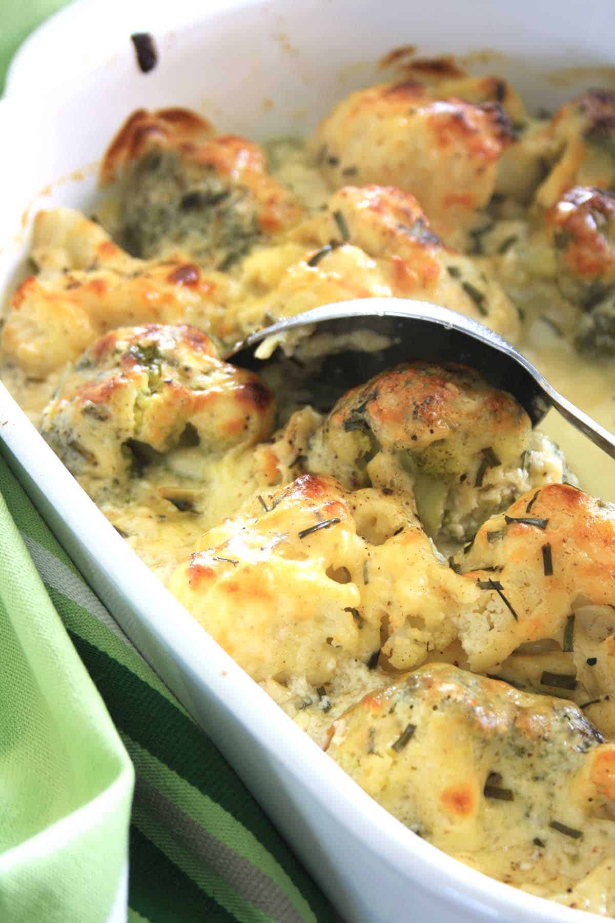 broccoli cauliflower cheese bake in a dish with a metal spoon for serving.