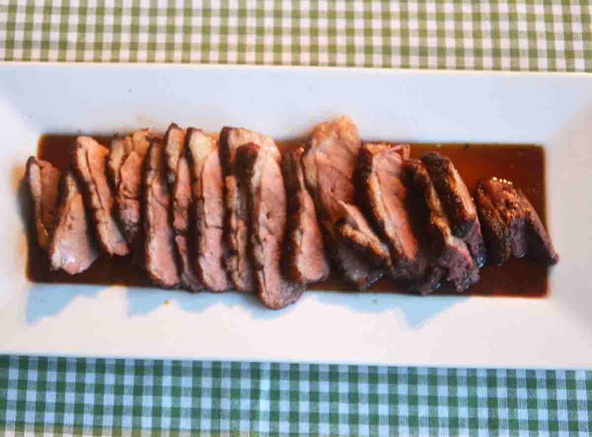 sliced duck on a plate in sauce.