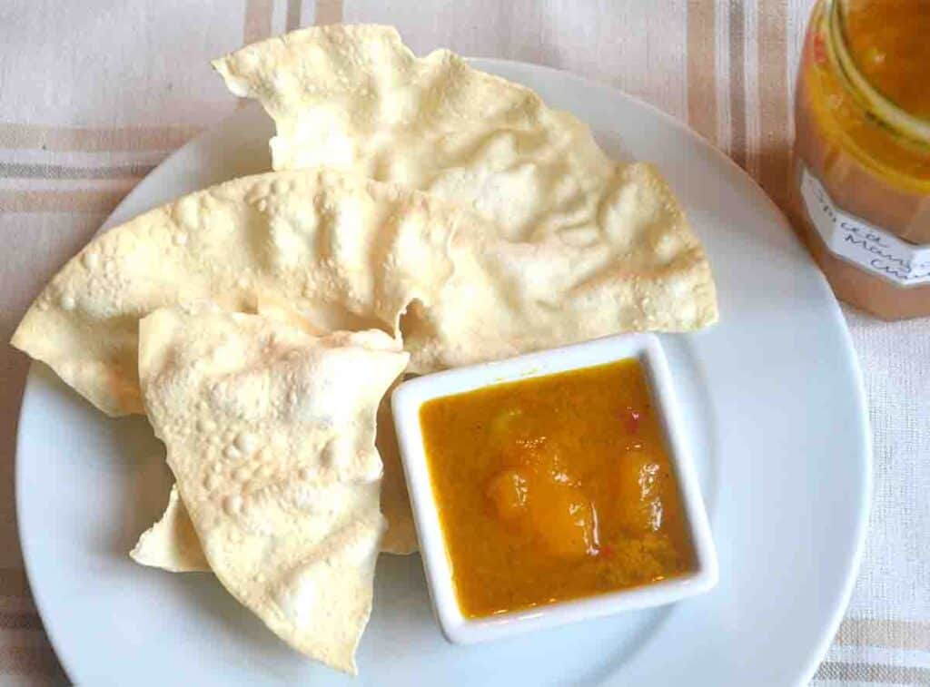 poppadums om a plate with small pot of spicy mango chutney with lime.