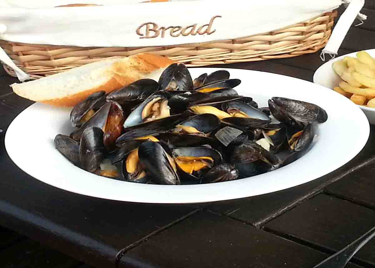 bowl of cooked shellfish with bread on the side and chips in the background.