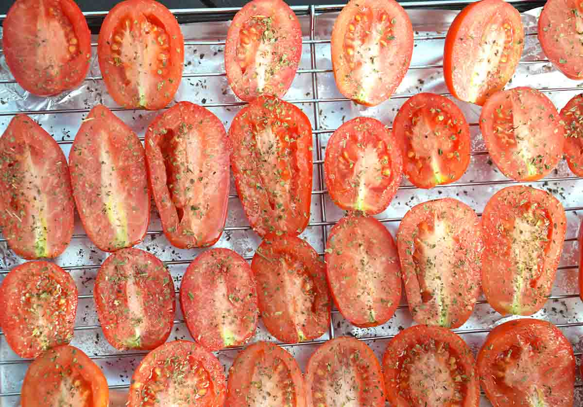 raw tomatoes sliced in half, cut side up on a grill rack.