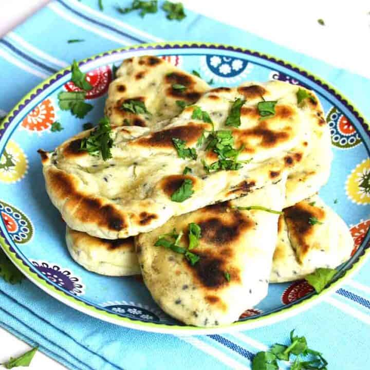 pile of homemade naan breads on a plate.