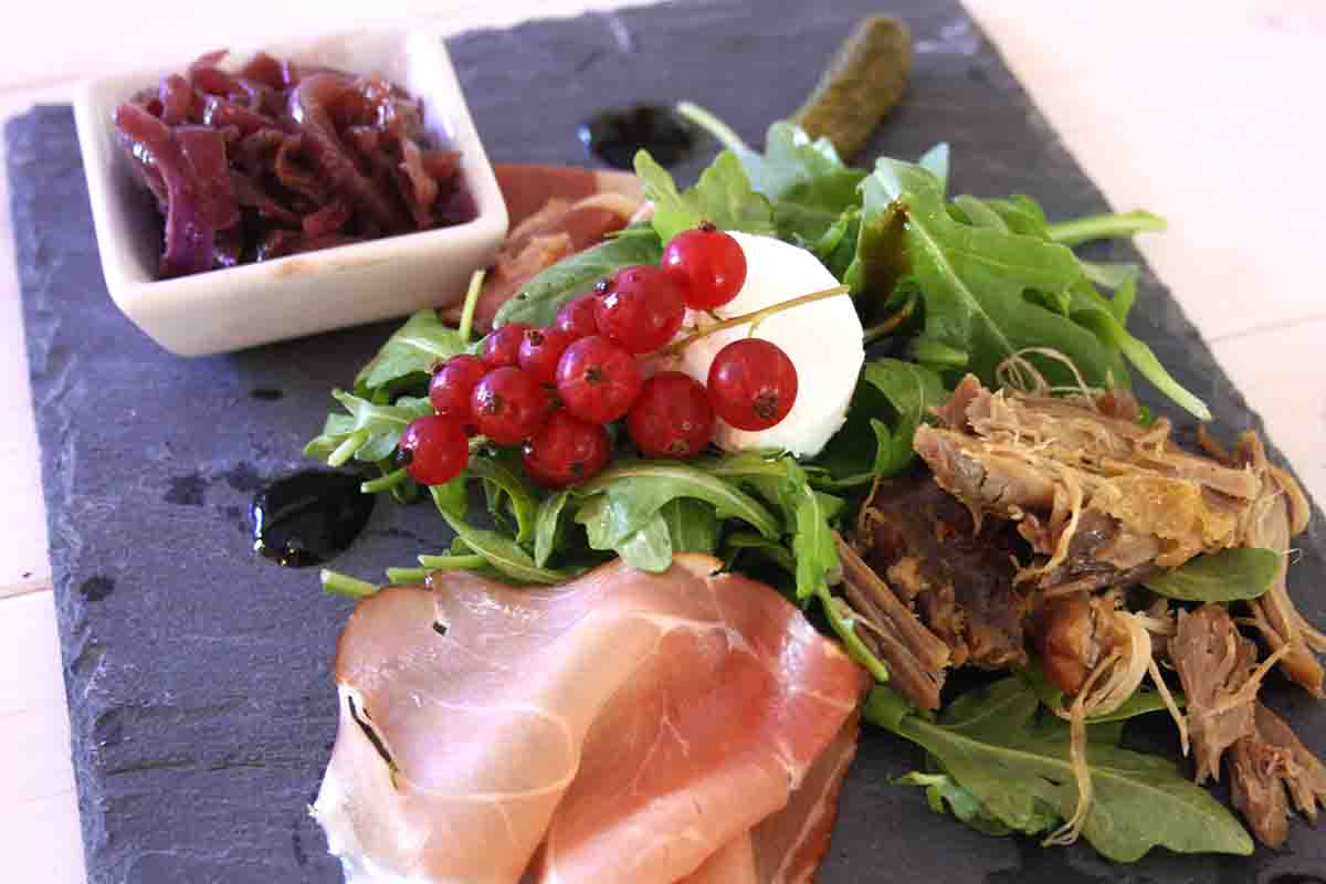 goat cheese, redcurrants, ham and shredded duck on a slate plate.