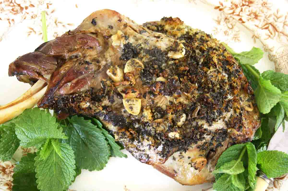 slow roast lamb kleftiko shoulder on a plate with fresh mint.