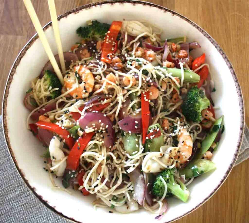 seafood chow mein in a large bowl with chop sticks.