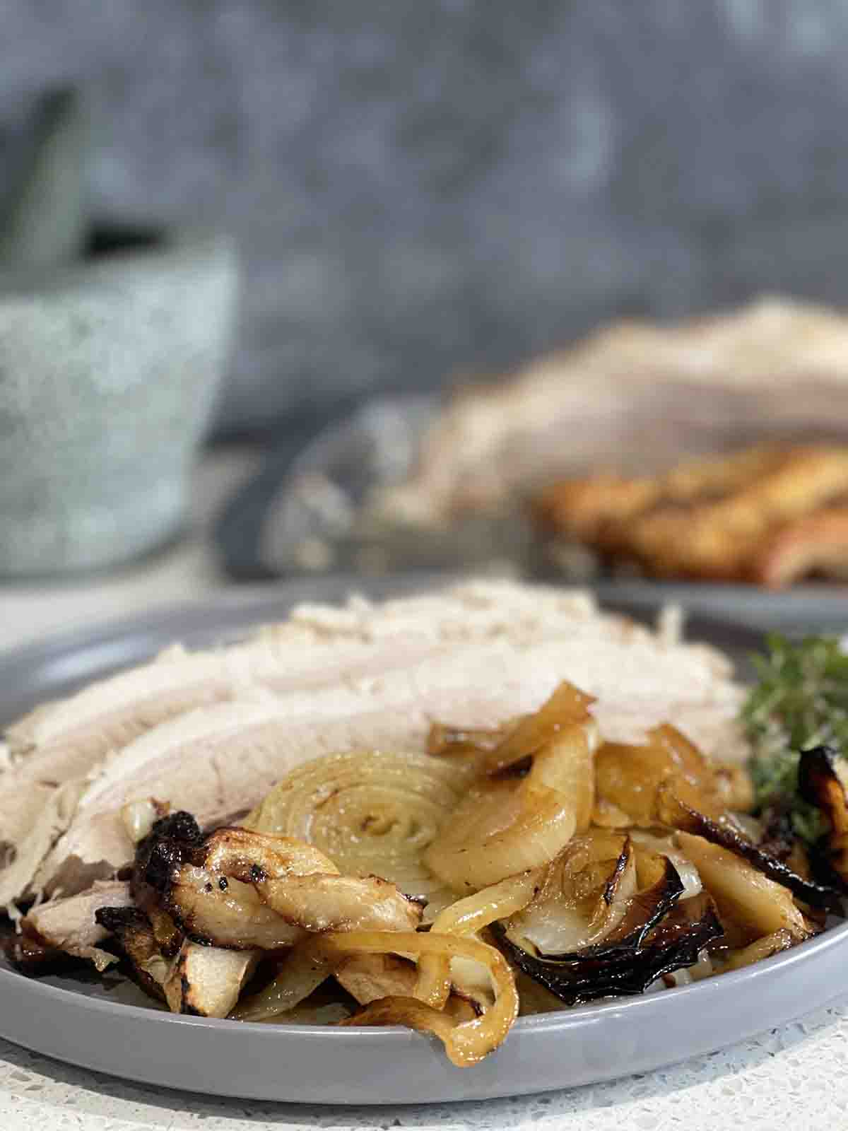 roast pork on a plate with apples and onions.
