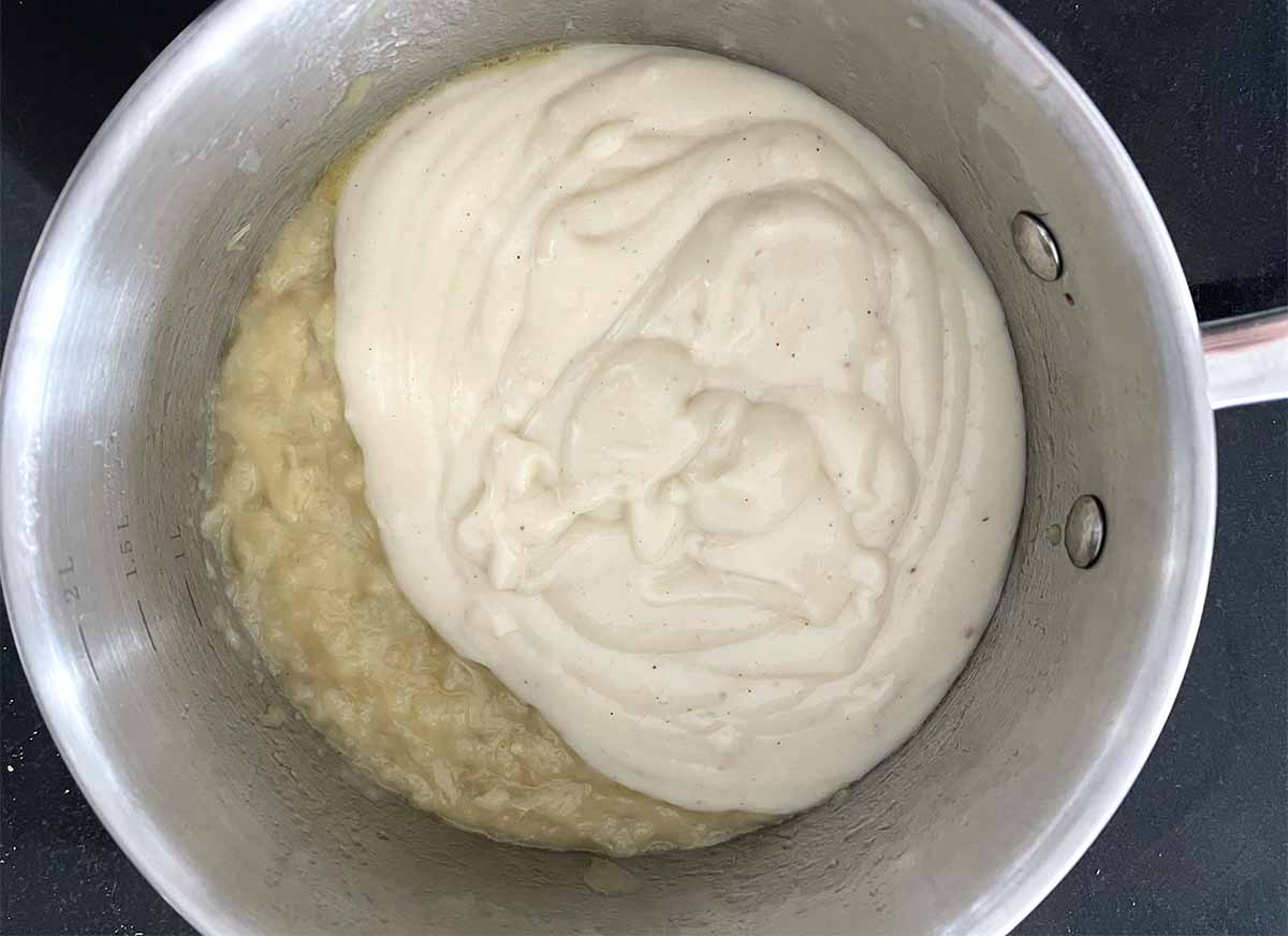 bechamel sauce added to onions in the saucepan.