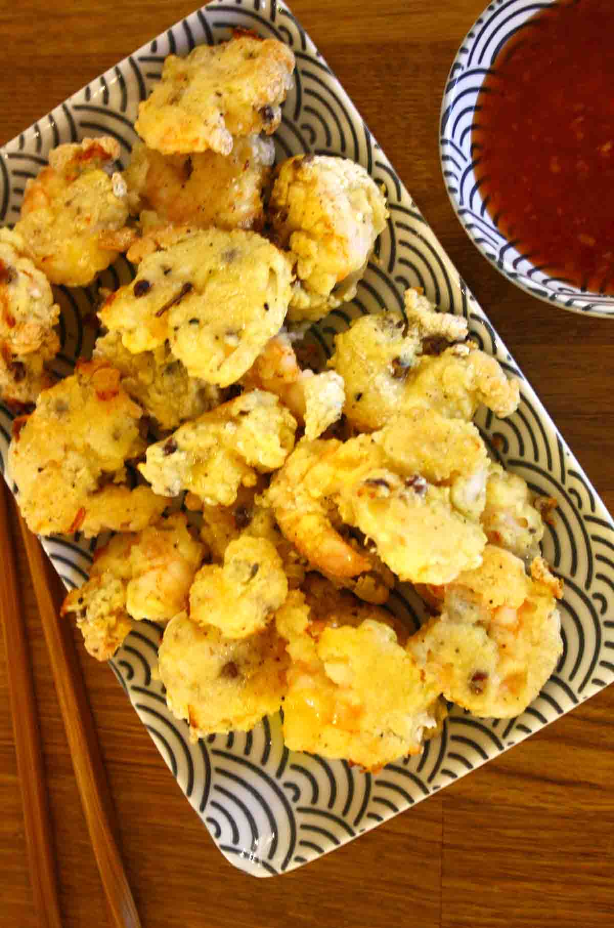 Sichuan prawns or Szechuan prawns on a plate with sauce in the background.