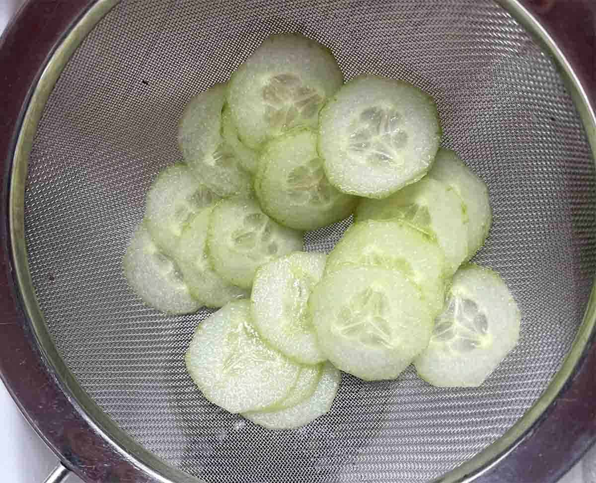 salted sliced cucumber draining in a sieve.