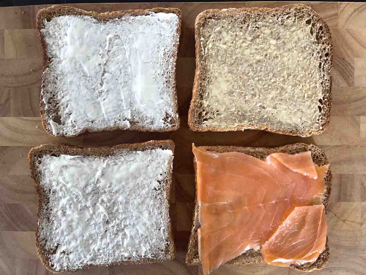 two slices of bread spread with cream cheese andtwo slices with smoked salmon.