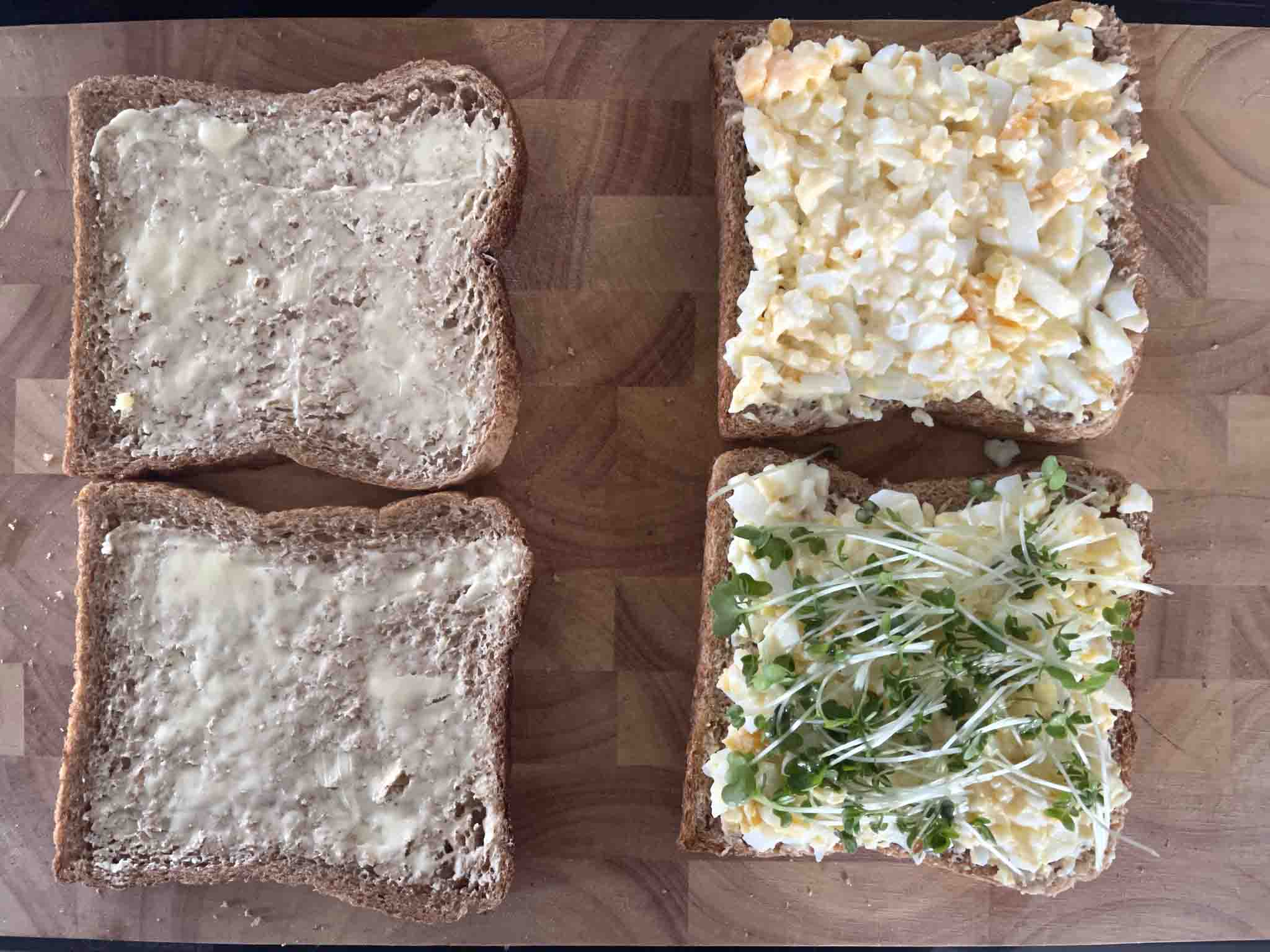 two buttered pices of bread and two pieces with eggm mayonnaise and cress.