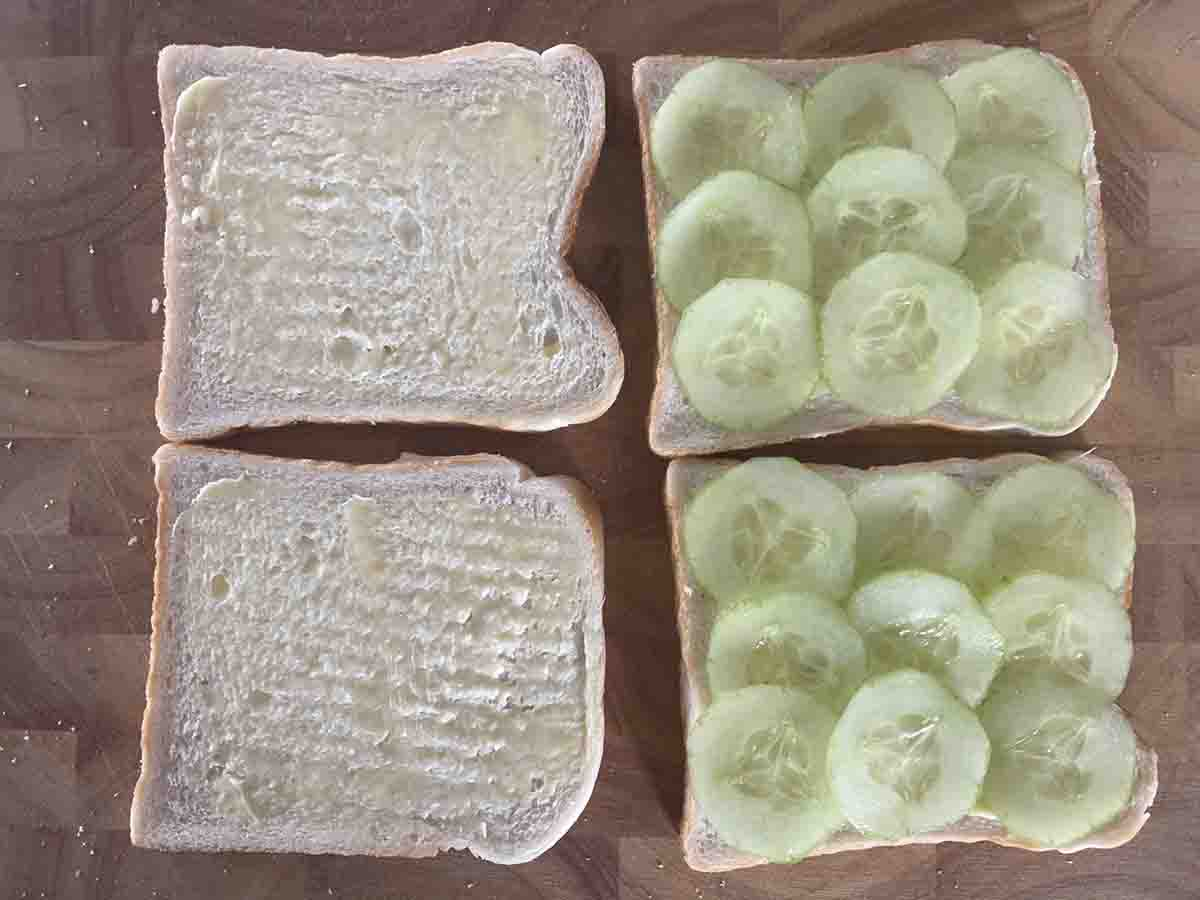 two slices of bread buttered and two slices with cucumber.