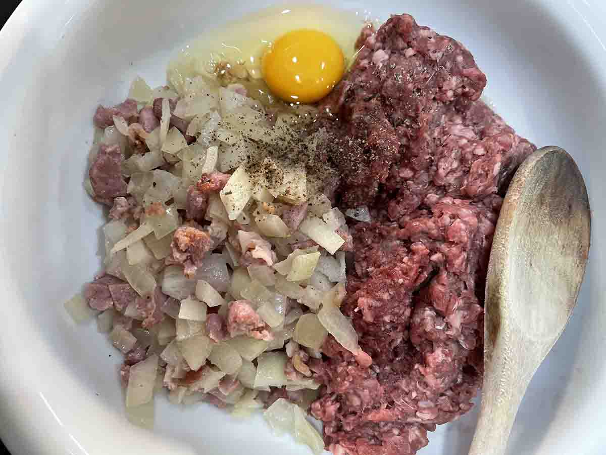 venison mince, cooked onion mixture, seasoning and egg in a bowl.