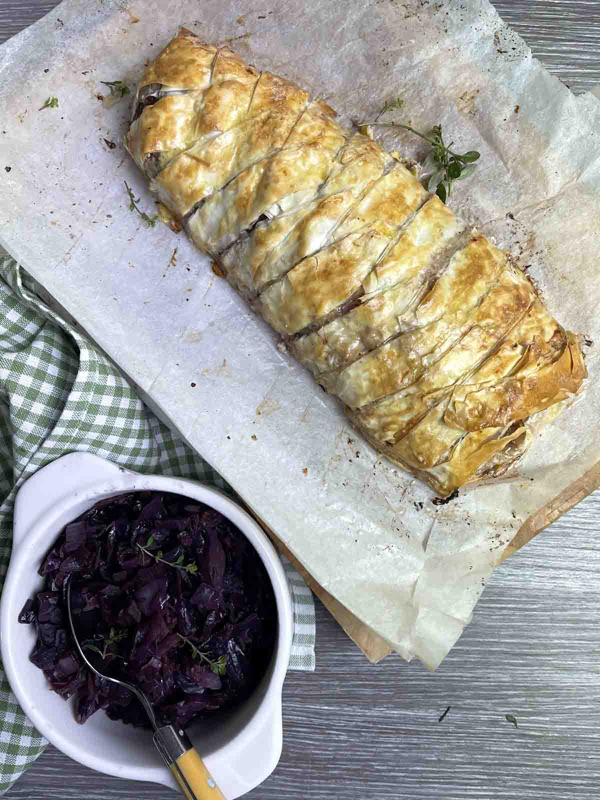 cooked venison sausage plait with a pot of red cabbage to the side.