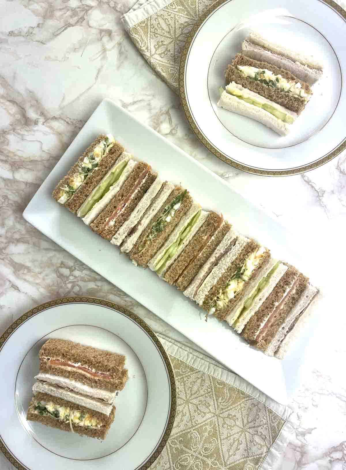 long plate of  finger sandwiches in rows and plates to the side with three sandwiches on.