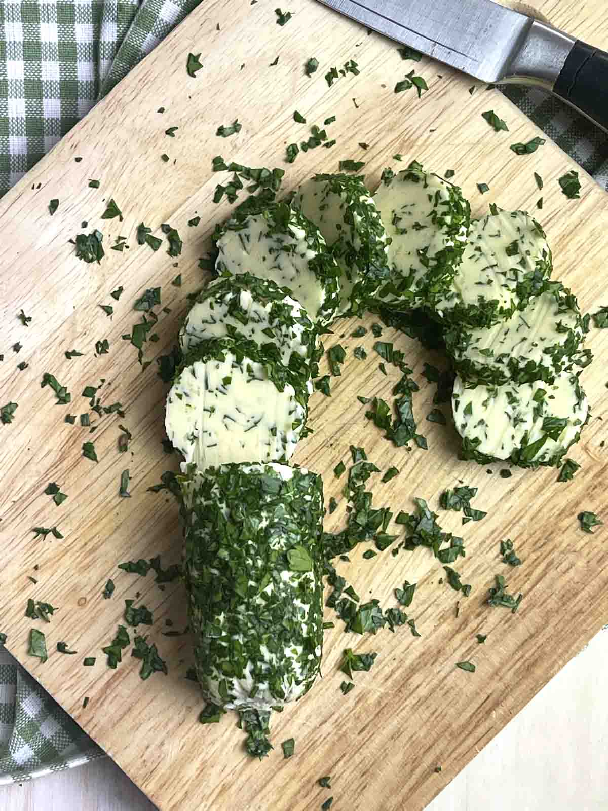 sliced parsley garlic flavoured butter log on a chopping board.