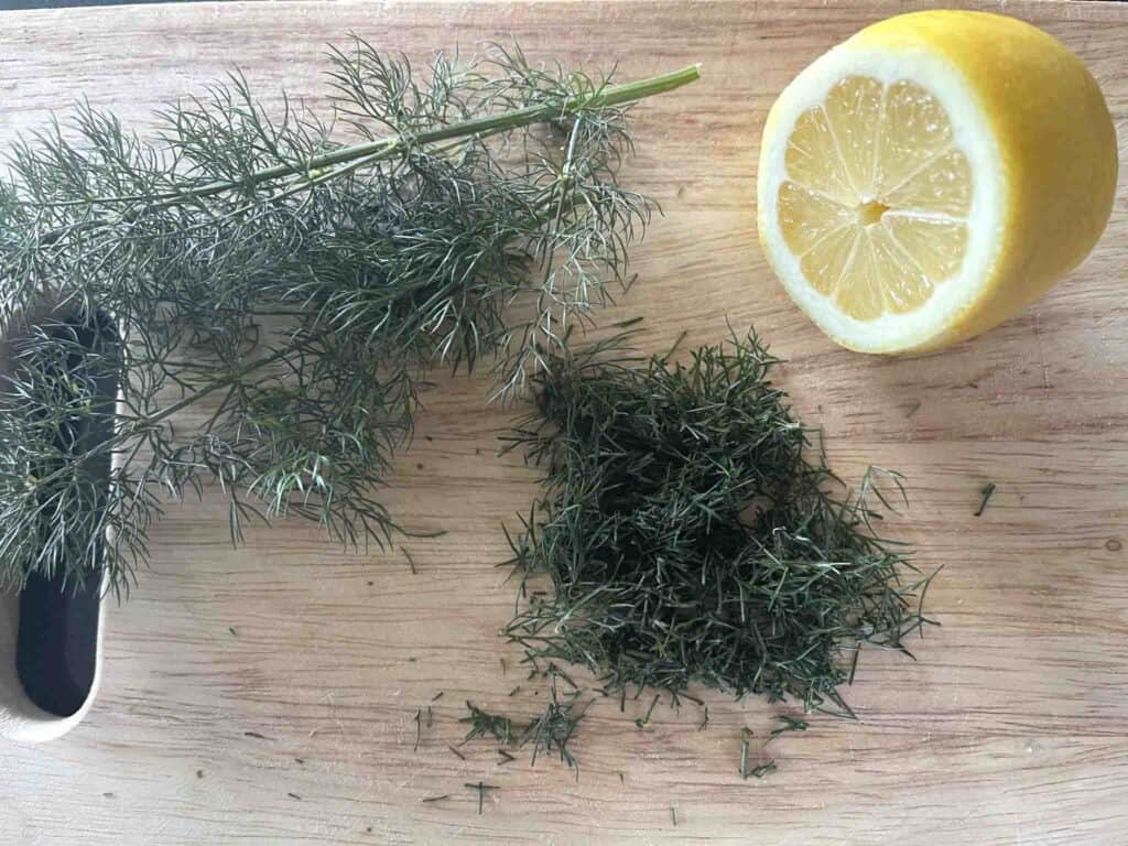 half a lemon and chopped dill on a board.