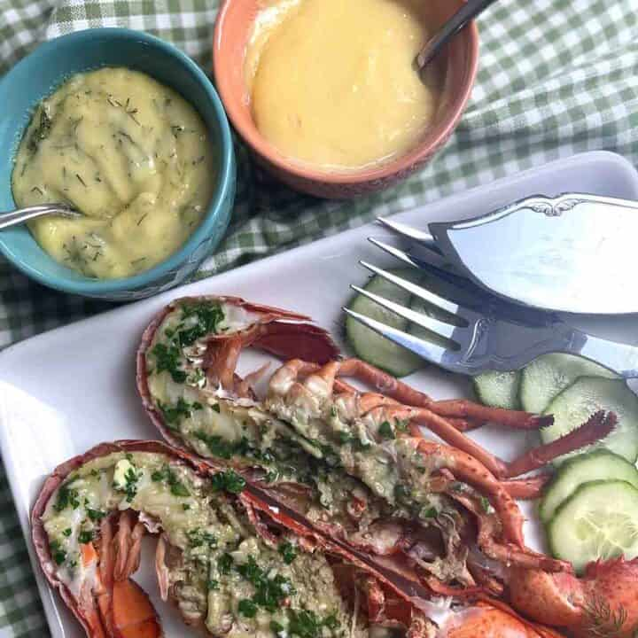 lobster on a plate with plain and dill mayonnaise in pots.
