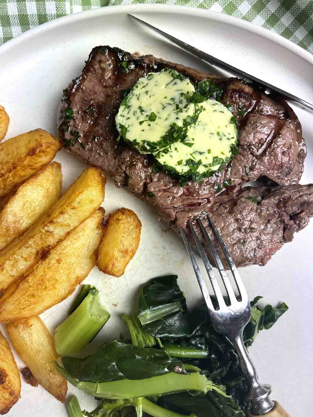 steak with garlic and herb compound butter on top.