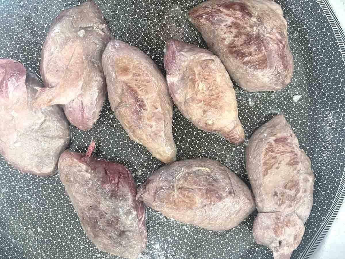 pan seared pigeon breast in a frying pan.