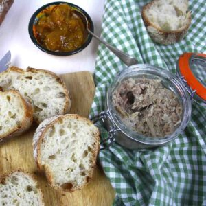 pot of pork rillettes with sliced bread, chutney and cucumber.