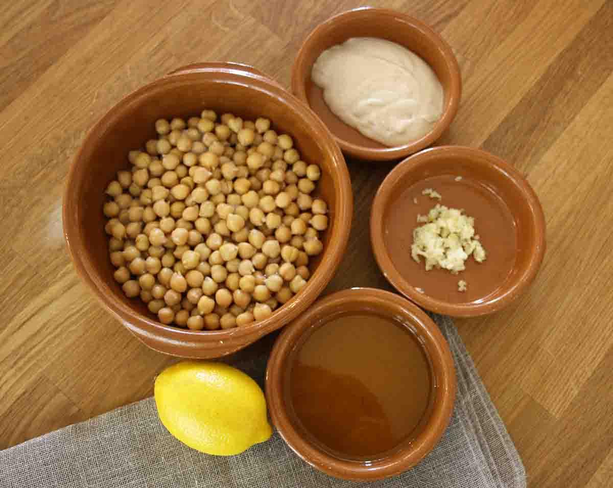 bowls of chickpeas, tahini, garlicoil and a lemon.