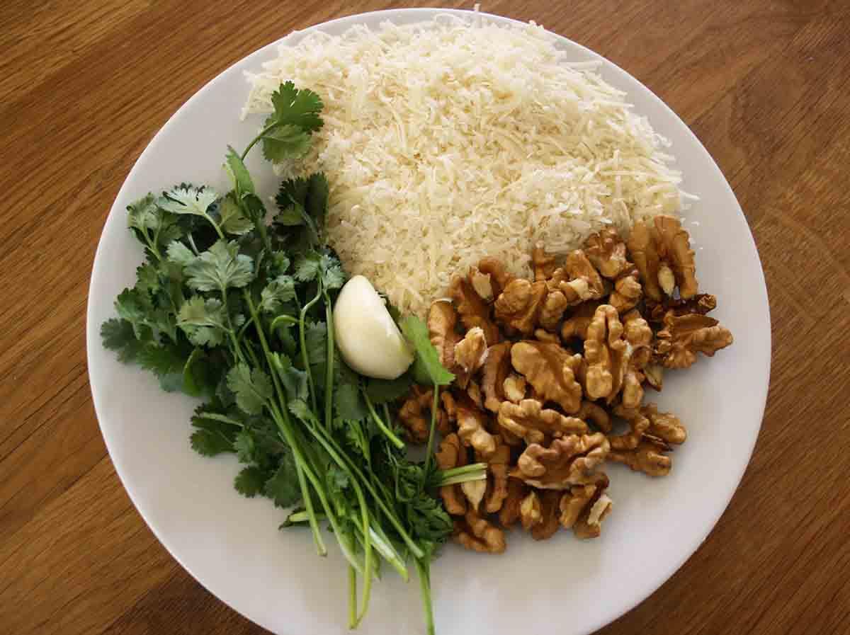 plate of ingredients including Parmesan, corander, walnuts and garlic.