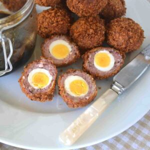 halved quail scotch eggs on a plate.