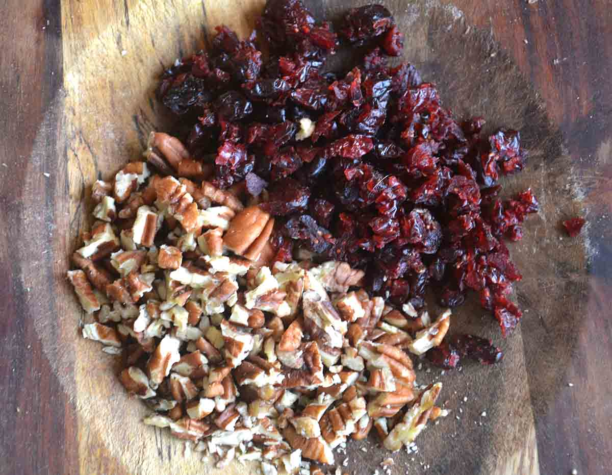 chopped cranberries and pecans on a board.