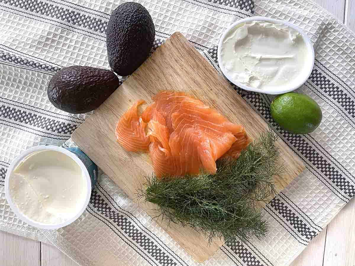 pile of salmon and dill on a board with pot of cream cheese, creme fraiche and avocadoes and lime.