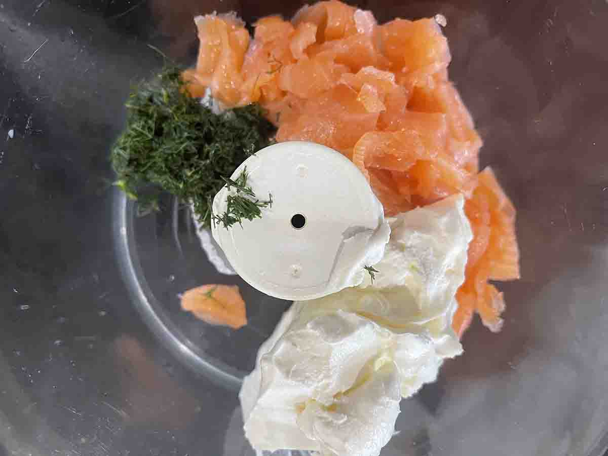 food processor bowl with smoked salmon, cream cheese and dill.