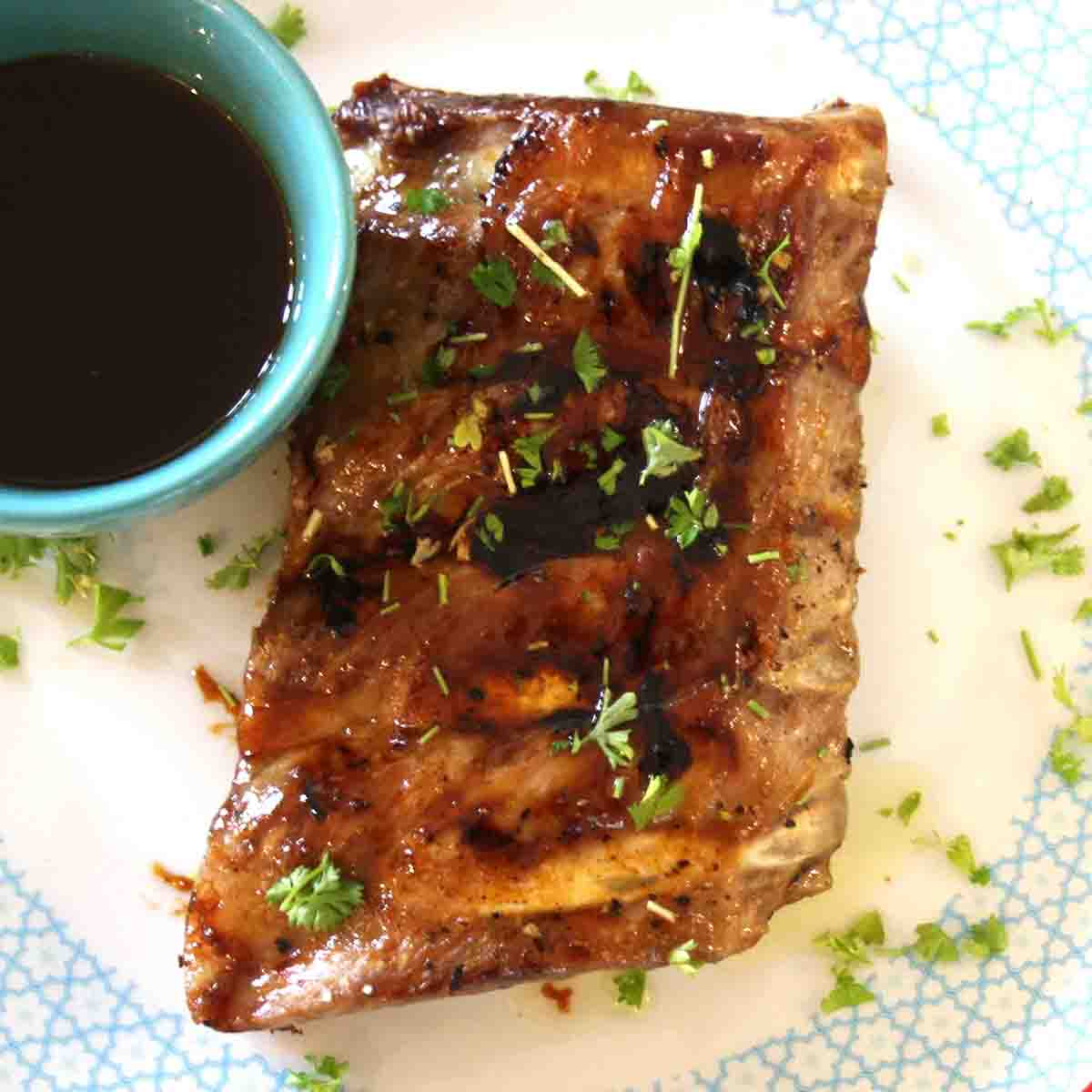 sticky bourbon ribs on a plate with sauce in a pot.