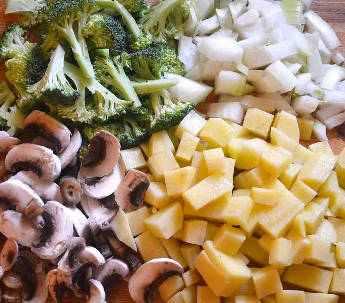 chopped broccoli, mushrooms and potatoes on a board.