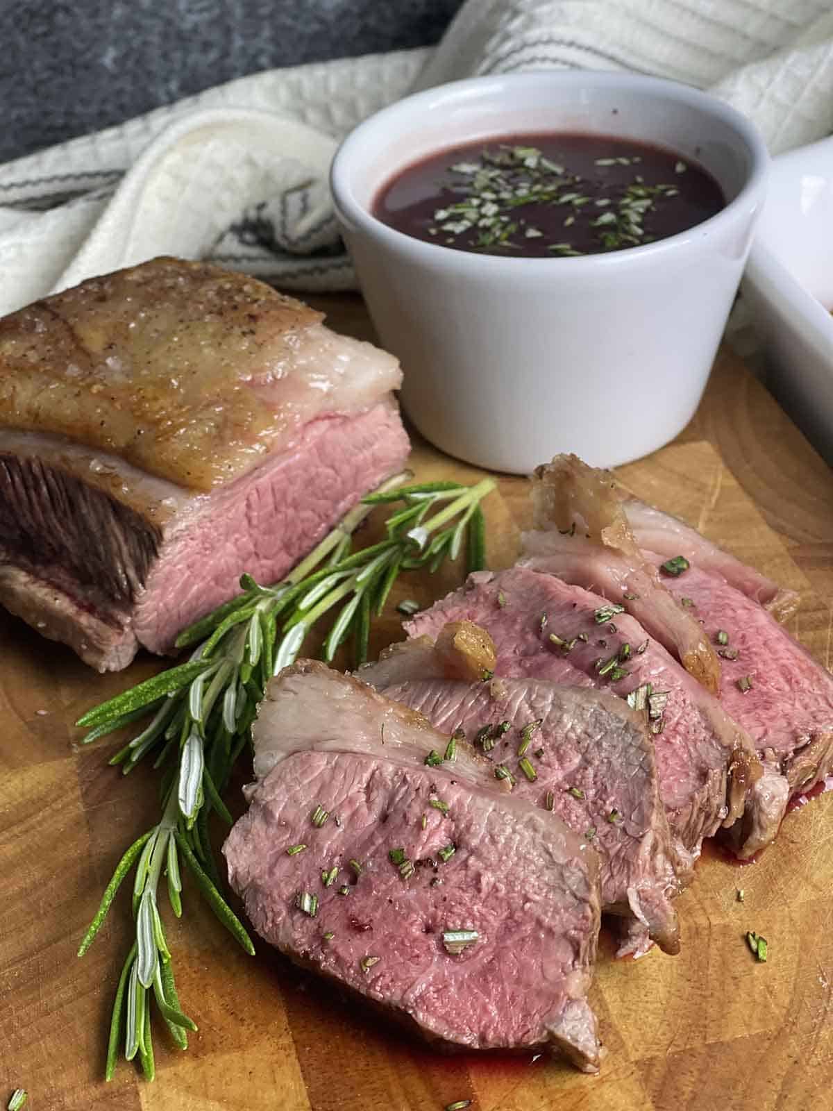 slices of cannon of lamb with a redcurrant sauce in a pot.