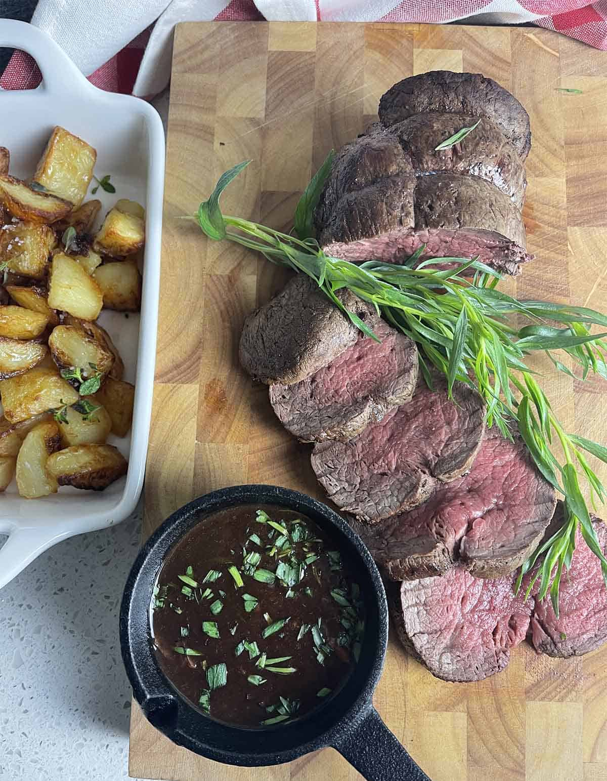 how to cook chateaubriand with porcini sauce with meat sliced on a board.
