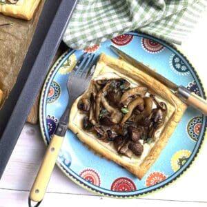 Vegetarian mushroom tart on a plate with cutlery.