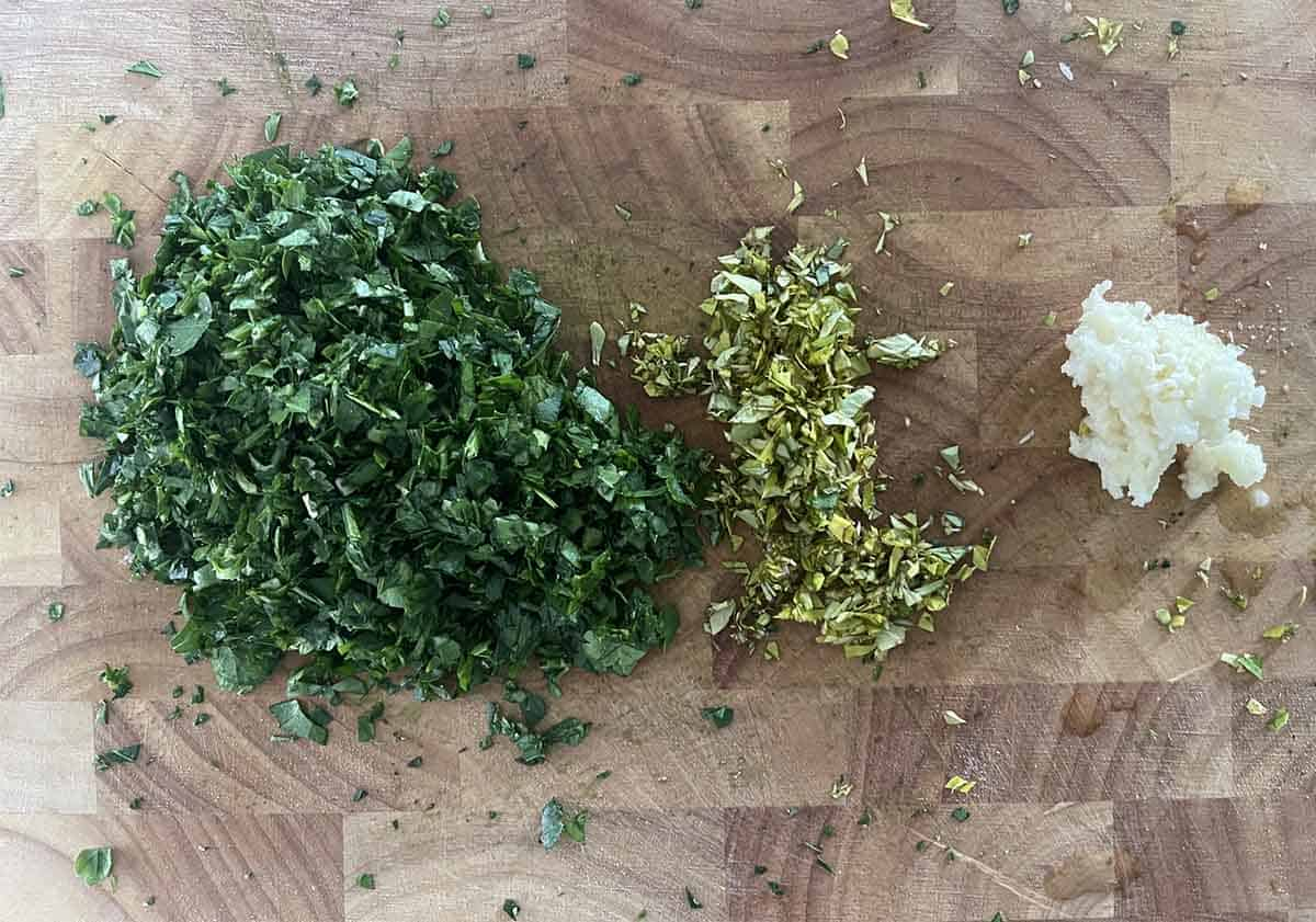 chopped parsley, oregano and garlic on a board.