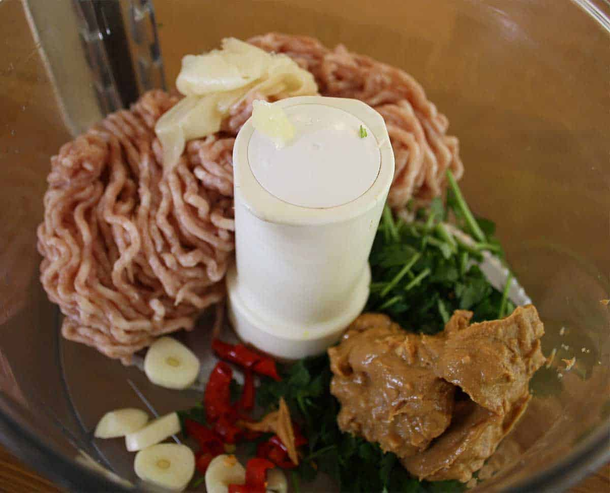 pork mince, garlic, chillies and other ingredients in a food processor bowl.