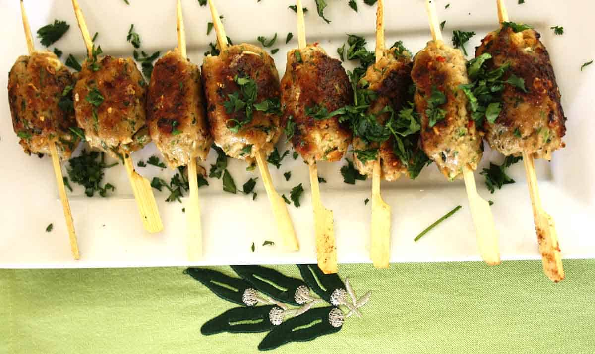 cooked pork skewers lined up on a white plate.