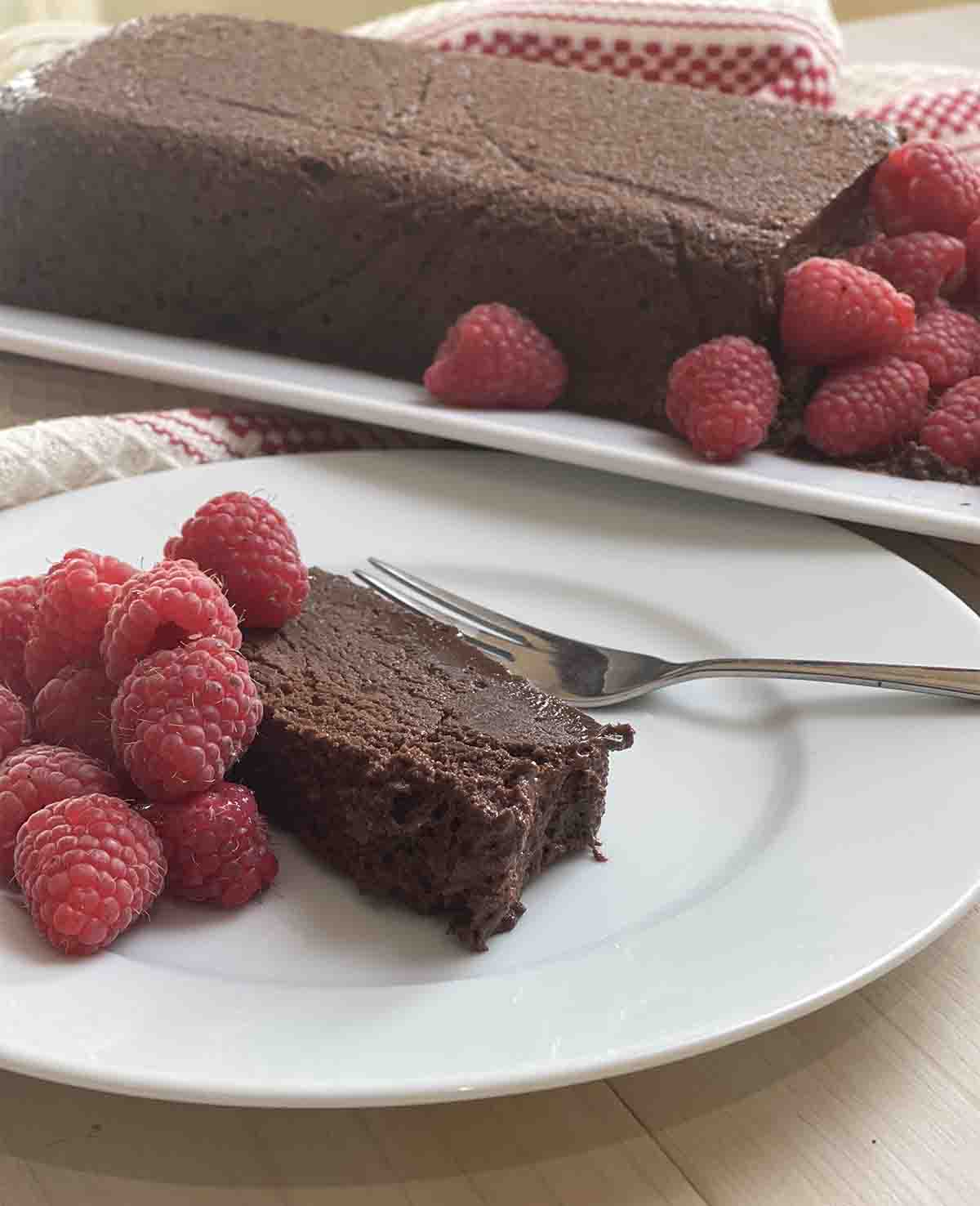 slice of chocolate marquise on a plate with raspberries and the rest of the dessert in the background.