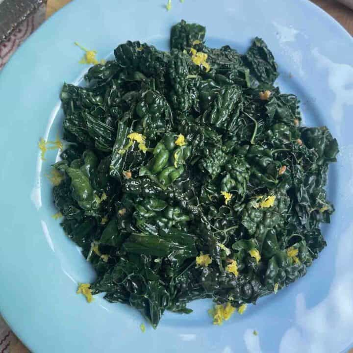 cooked cavolo nero with browned butter on a plate.