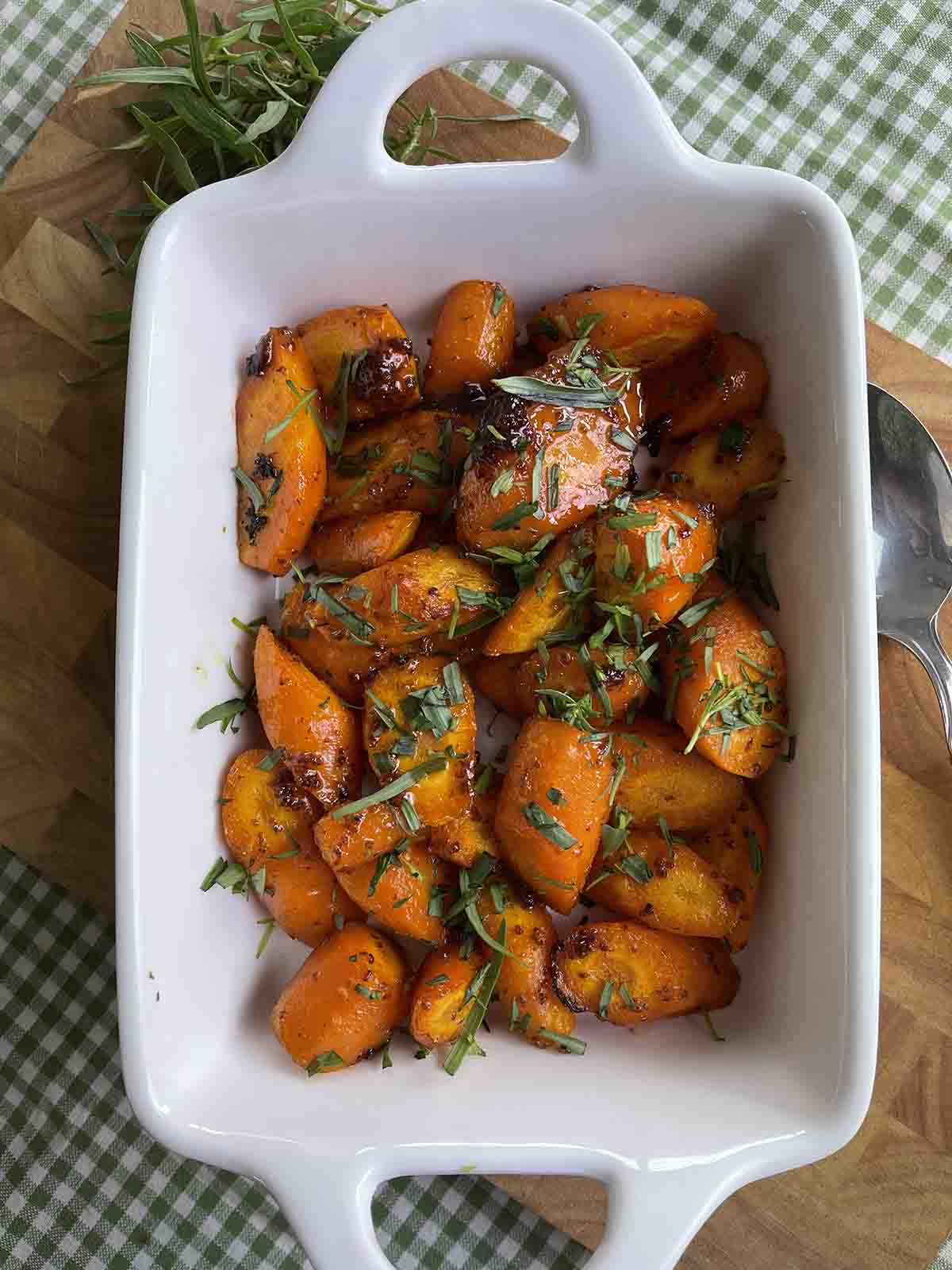 honey roasted carrots in a dish with a serving spoon.