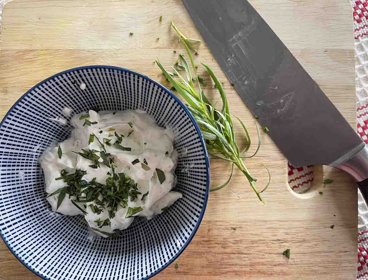 cream cheese in a bowl with tarragon and a knife to the side.