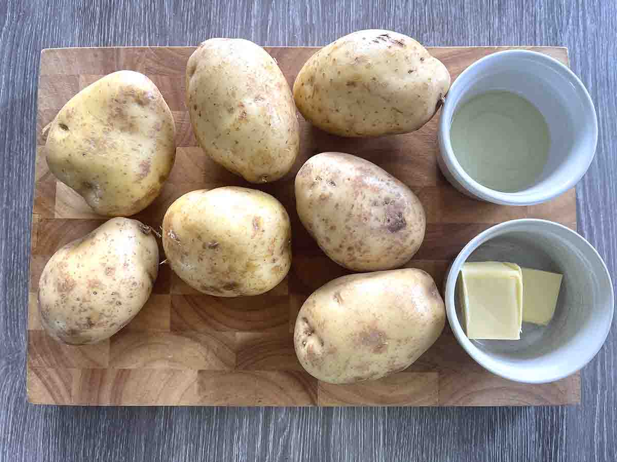 potatoes and a pot of oil and pot of butter on a board.