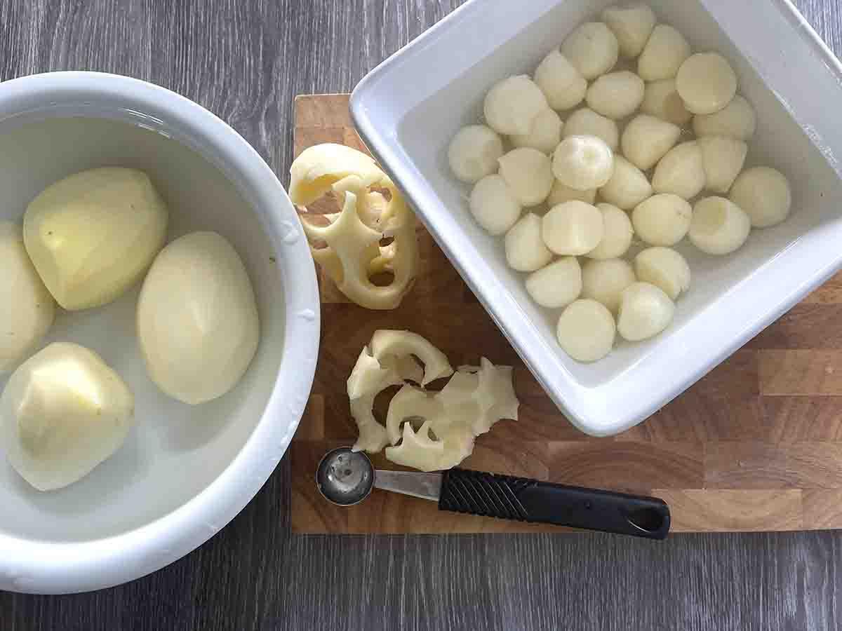 bowl of peeled potatoes and bowl of potato balls.