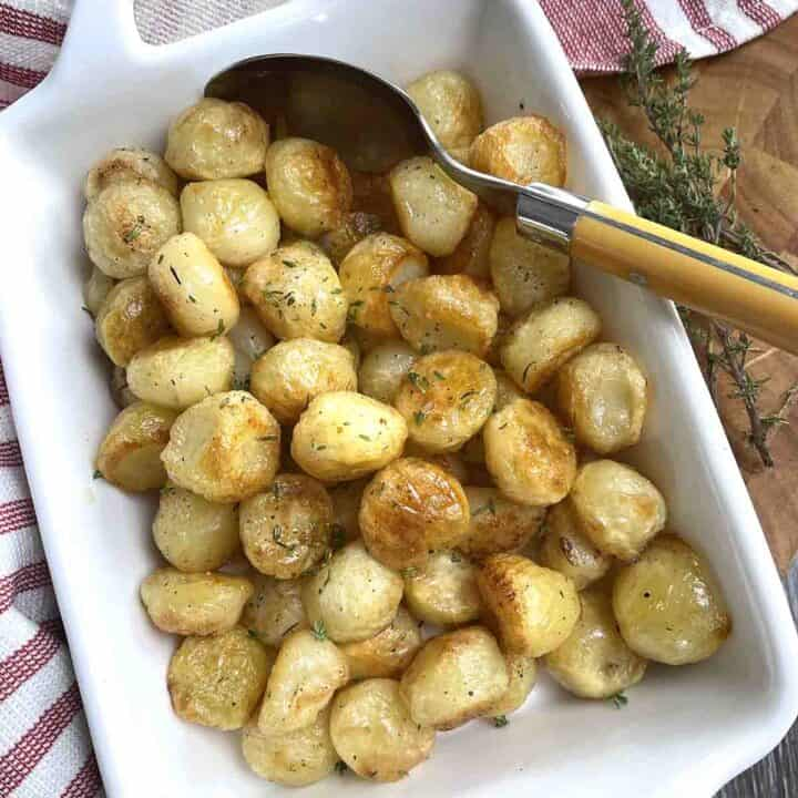 Potatoes Parisienne in a white serving dish with a spoon.